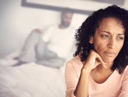 woman staring into distance with man in background